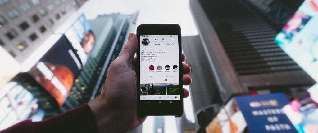 Smartfon z aplikacją Instagram na tle budynków w centrum miasta